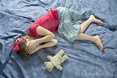 Little upset crying girl lying on the bed