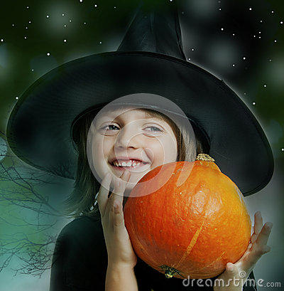 Little witch holding a pumpkin