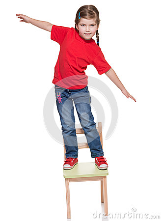 Littlr gitl standing on a chair and balancing