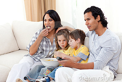 Lively family watching TV and eating chips