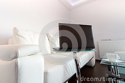 Living room with white leather sofa and laptop