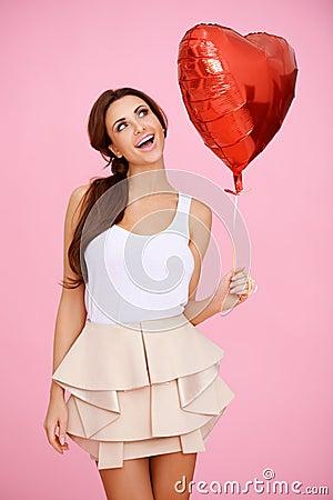 Livlig brunett med en röd hjärtaballong
