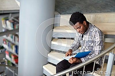 https://thumbs.dreamstime.com/x/livre-de-lecture-africain-de-garon-ou-d-homme-d-tudiant-la-bibliothque-76569271.jpg