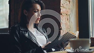 Livre de lecture attrayant d'étudiante dans se reposer de détente de café seule à la table banque de vidéos