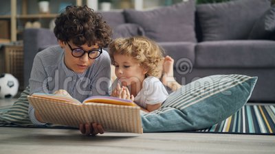 Livro de leitura da mamã da jovem mulher ao menino curioso que discute a história no assoalho em casa video estoque