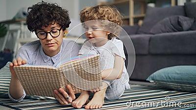 Livro de leitura de inquietação da mamã ao menino curioso pequeno que relaxa no assoalho na casa clara vídeos de arquivo