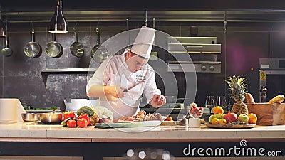 Lo chef taglia il piatto preparato con un coltello stock footage
