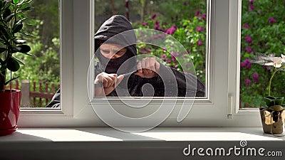 Lo scassinatore si rompe in una casa attraverso la finestra archivi video