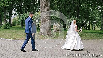 Lo sposo va seguire la sua sposa felice nel parco stock footage
