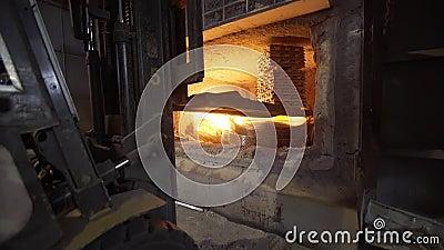 Loader laadt aluminium ingots in een hoogoven Aluminiumgieteroven geladen met metaal Rood opvlammen gloeien stock footage
