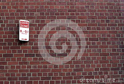 Loading zone sign on brick wall
