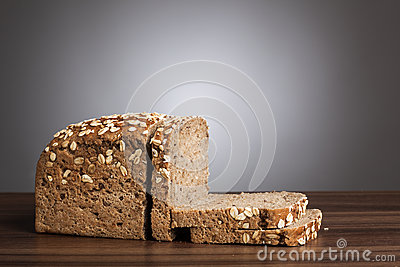 Loaf and slices of wholemeal bread on table