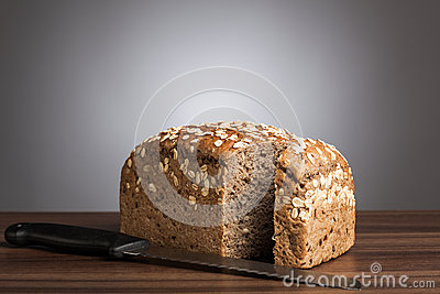Loaf of wholemeal bread with knife on table