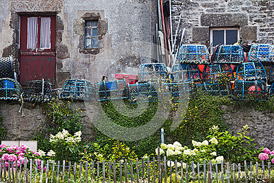 Lobster pots in front of a stone house
