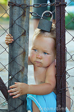 Free Locked Baby Trying To Escape Through Wire Fencing Royalty Free Stock Images - 23810029