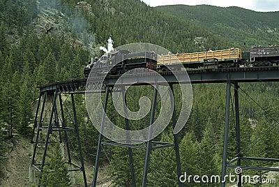 Locomotive and Boxcars on Trestle Bridge Editorial Stock Photo