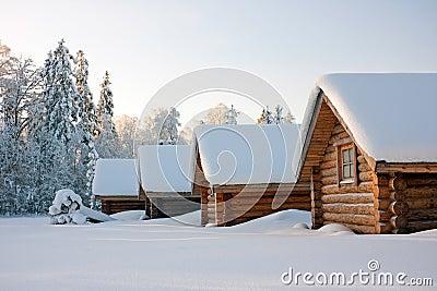 Log cabins under snow in winter