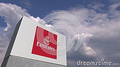 Logo di EMIRATES AIRLINES su un supporto contro il cielo nuvoloso, animazione editoriale video d archivio