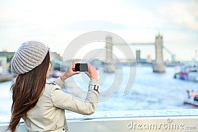 London woman tourist taking photo on Tower Bridge