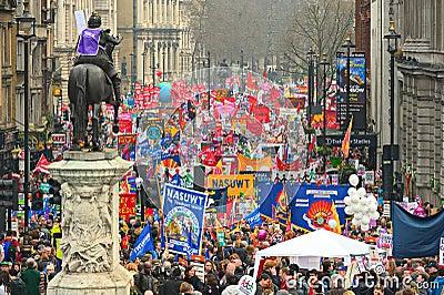 LONDRES - MARÇO 26: Os protestadores marcham abaixo de Whitehall de encontro às despesas públicas cortam dentro uma reunião -- Mar Fotografia Editorial