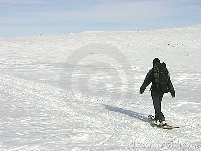 Lone man with a backpack snowshoeing