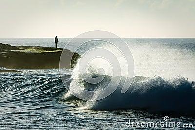 Lone sea fisherman on rocks