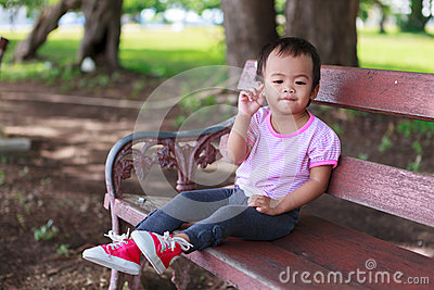 Lonely Asian baby girl sitting on bench