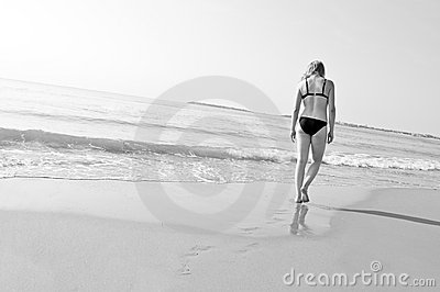 Lonely girl walks on the beach