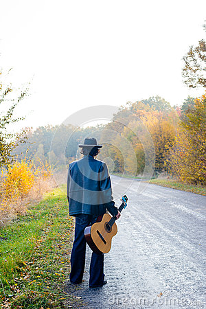 Free Lonely Guitarist Looking At Empty Country Road In Stock Photo - 57393610
