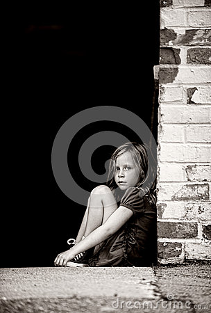 Lonely Little Girl Sitting Against Wall Stock Photography