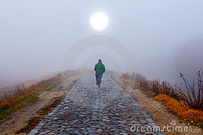 Lonely man running toward the sun on misty morning