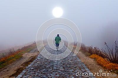 Lonely man running toward the sun on misty morning