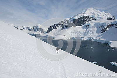 Lonely man walking along the snow slope