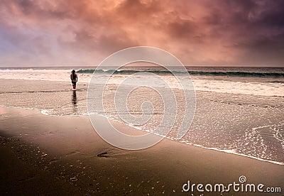 Lonely man walking at beach