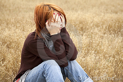 Lonely sad red-haired girl at field