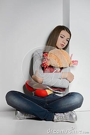 Lonely teenage girl. Sad teenage girl sitting on the floor and h