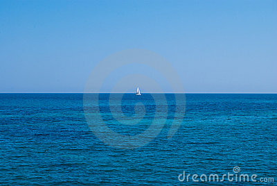 Lonely yacht in an open sea under solid blue sky