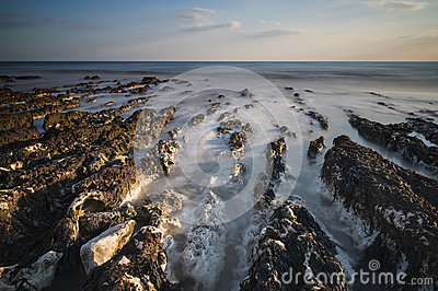 Long exposure landscape rocky shoreline at sunset