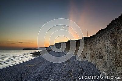 Long exposure landscape rocky shoreline at sunset