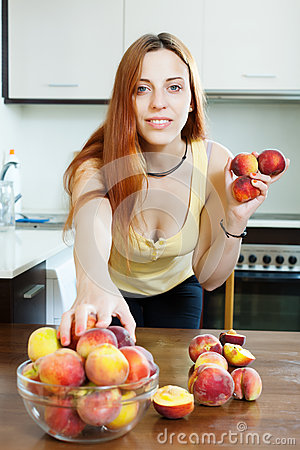 Long-haired woman taking peaches
