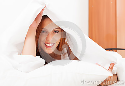 Long-haired woman under white sheet