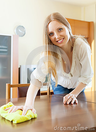 Long-haired woman wiping the dust from table