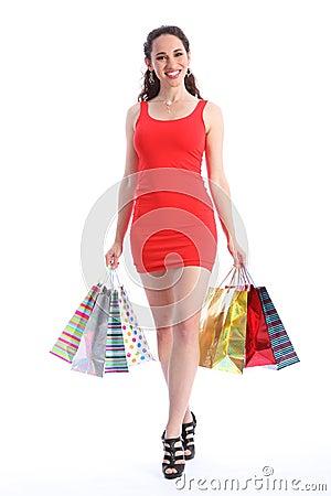 Long legged young woman walking with shopping bags