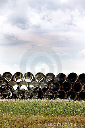Long Pipe Stacked Next to Highway
