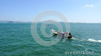 Long tail boat with the sailor on the open sea in Thailand near the Koh Muk Island