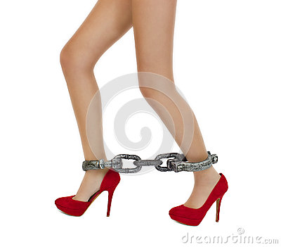 Long woman legs in stylish red shoes with shackles