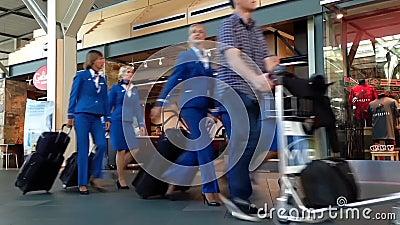 Loodsen en stewardess met bagage binnen YVR-luchthaven stock videobeelden