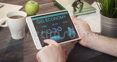 Looking at gig economy information using tablet computer at desk. Looking at gig economy information using tablet computer at the desk stock video