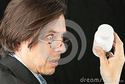 Looking Over Reading Glasses To Read Pill Bottle