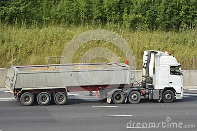 Lorry with articulated loaded tipper trailer carrying sand